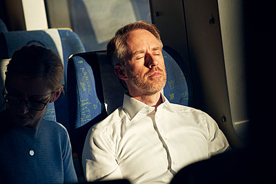 Man sitting in train with eyes closed - p312m2207701 by Johan Alp