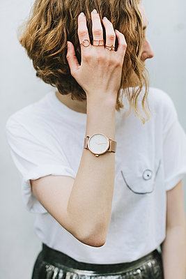 Portrait of red haired woman wearing rings and wristwatch looking away - p429m1569679 by Lena Mirisola