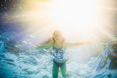 Caucasian girl swimming underwater in swimming pool - p555m1411532 by John Fedele