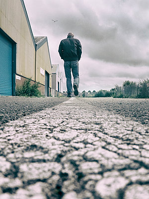 Rearview man walking through industrial estate - p597m1589502 by Tim Robinson