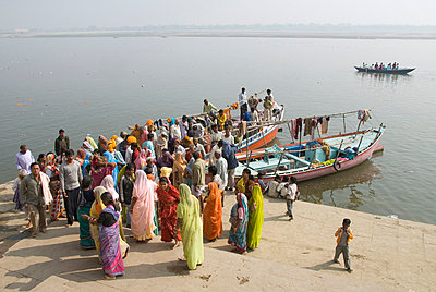 Women mourners take to a boat on the River Ganges while a cremation takes place, Varanasi, Uttar Pradesh state, India, Asia - p8710349 by Tony Waltham