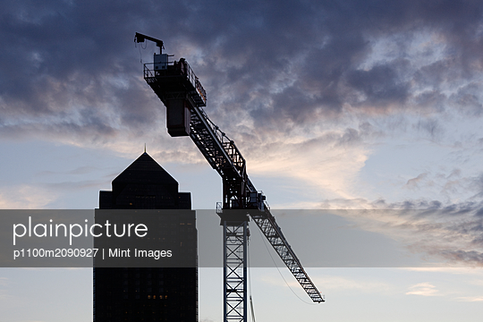 Tower Crane with Building Silhouette in Background - p1100m2090927 by Mint Images