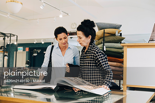 Woman assisting customer choosing wallpaper sample in store - p426m2149192 by Maskot