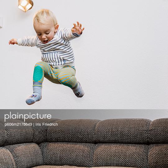 Little boy jumping from sofa back - p606m2178649 by Iris Friedrich