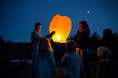 Children looking at parents with illuminated paper lantern - p1166m1095818f by Cavan Images