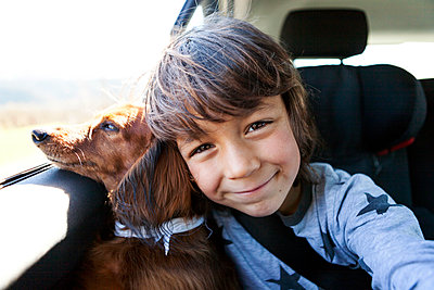 Portrait of smiling little boy sitting with his long-haired dachshund in a car - p300m1129104 von Valentina Barreto