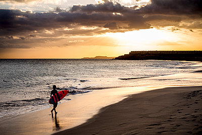 Spain, Tenerife, boy carrying surfboard on the beach at sunset - p300m1189009 by Simona Pillola