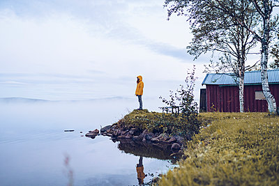 Sweden, Lapland, man wearing  windbreaker standing at water's edge looking at distance - p300m2059318 by CSSHOT