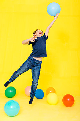 Full length of boy catching balloon while playing against yellow background - p300m2199113 by Josep Rovirosa