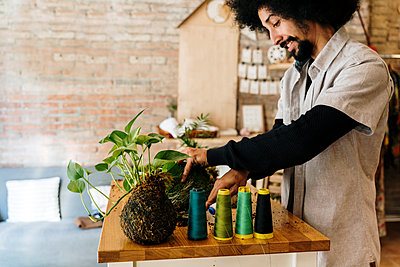 Man with kokedama plant and spools on table at home - p300m2273500 by VITTA GALLERY