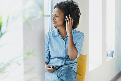 Woman adjusting headphones while sitting with digital tablet at home - p300m2277496 by Steve Brookland