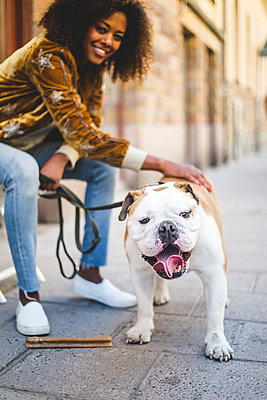 Close-up of English bulldog standing with woman sitting in background - p426m2046352 by Maskot