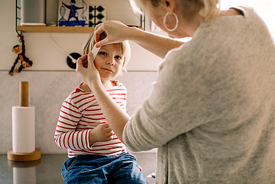 Mother applying bandage on daughter's face at home - p426m2074560 by Maskot