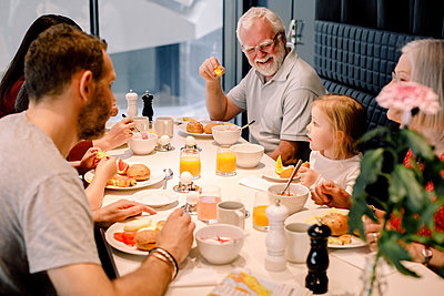 High angle view of multi-generation family having food at table in restaurant - p426m2102057 by Maskot