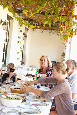 Family eating at table outdoors - p42916507f by GretaMarie