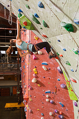 Mixed race teenage girl climbing rock wall - p555m1312137 by Don Mason
