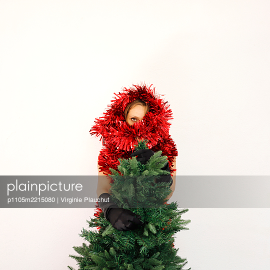 Woman with christmas tree and garland around her head, portrait - p1105m2215080 by Virginie Plauchut