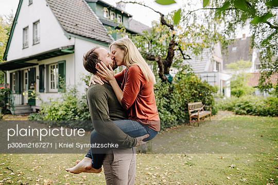 Happy couple kissing in garden, in front of their dream house - p300m2167271 von Kniel Synnatzschke