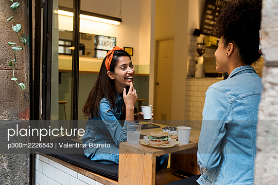 Smiling women talking while sitting by window at cafe - p300m2226843 by Valentina Barreto