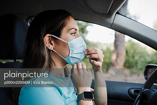 Young woman wearing protective face mask in car during COVID-19 - p300m2293439 by Eva Blanco