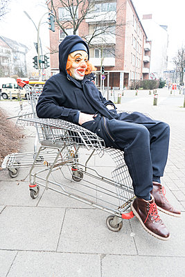 Clown sitting in shopping trolley - p075m2071220 by Lukasz Chrobok