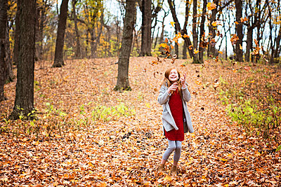 Young Red Hair Girl Playing Outside in Fall Leaves - p1166m2147065 by Cavan Images