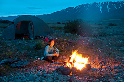woman sitting by campfire in Iceland - p1166m2279423 by Cavan Images