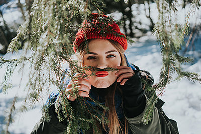 Young woman fooling around with conifer tree branch - p1184m1424095 by brabanski