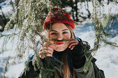 Junge Frau macht Unfug mit Zweigen eines Nadelbaums - p1184m1424095 von brabanski