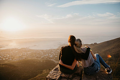 South Africa, Cape Town, Kloof Nek, two women sitting on rock at sunset - p300m2081041 by letizia haessig photography
