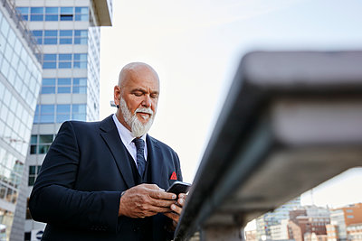 Elegant businessman using smartphone in the city - p300m2081163 by Rainer Holz