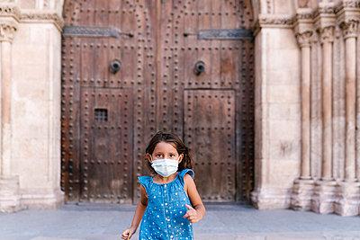 Girl wearing mask running in front of historic door - p300m2220685 by Ezequiel Giménez