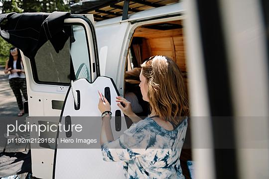 Female surfer preparing surfboard at camper van - p1192m2129158 by Hero Images