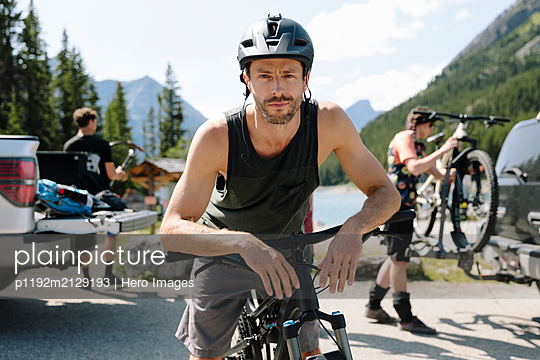 Portrait confident man with mountain bike in sunny parking lot - p1192m2129193 by Hero Images