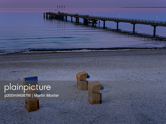 Germany, Schleswig-Holstein, Scharbeutz, Sea bridge and roofed wicker beach chairs at beach - p300m940876f by Martin Moxter