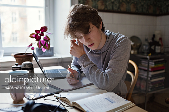 Serious teenage boy reading book while doing homework at home - p426m2101651 by Maskot