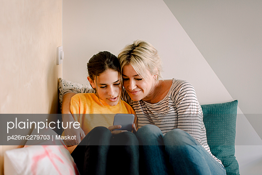 Mature woman sitting with daughter using smart phone in bedroom at home - p426m2279703 by Maskot