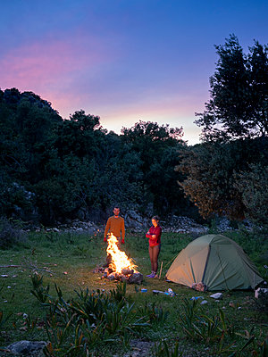 Two friends enjoying a campfire in dusk against trees and evening sky - p1166m2106733 by Cavan Images