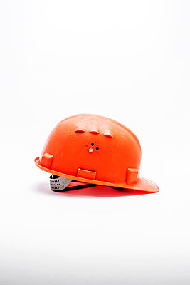 A worn, scratched and dirty orange hard hat or safety helmet on a white background - p1302m2126953 by Richard Nixon