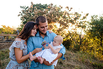 Portrait of young family with baby at sunset light - p1363m2175828 by Valery Skurydin
