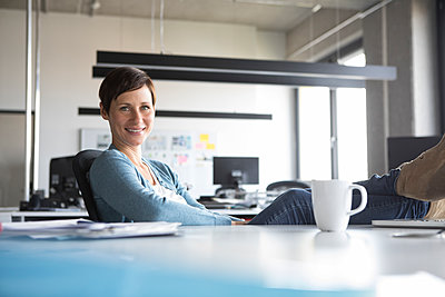 Portrait of smiling businesswoman in office - p300m1206125 by Rainer Berg