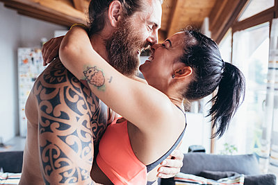 Bearded tattooed man with long brunette hair and woman with long brown hair standing indoors, hugging and kissing. - p429m2202136 by Eugenio Marongiu
