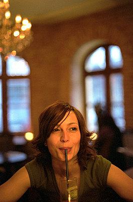 Brownhaired Woman drinks through a Straw - Restaurant - Beverages  - p4901072 by Felbert & Eickenberg