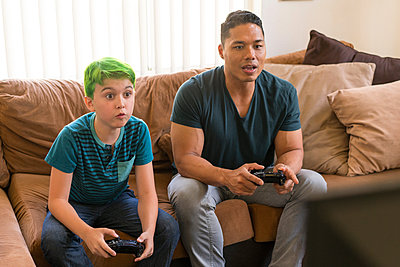 Father and son playing video game on sofa - p924m1155266 by Raphye Alexius