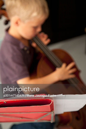 Boy playing cello with sheet music in the foreground - p301m714547f by Maria Jauregui Ponte