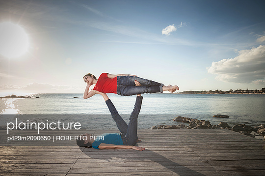 Women practising acro yoga at seaside - p429m2090650 by ROBERTO PERI