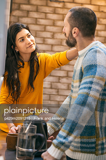 Hipster couple having coffee and talking in kitchen - p429m2091215 by Frank and Helena