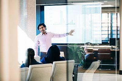 Businessman giving presentation in meeting seen through window - p1166m1403697 by Cavan Images
