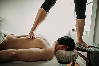 massage therapist uses ashiatsu method feet to treat patient's back - p1166m2163415 by Cavan Images