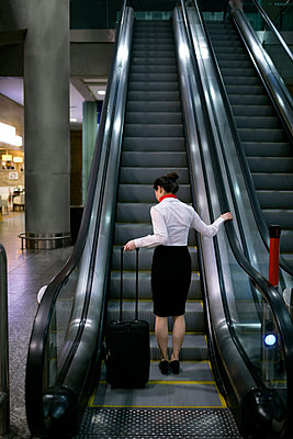 Woman standing on escalator with luggage at airport - p1315m1566709 by Wavebreak